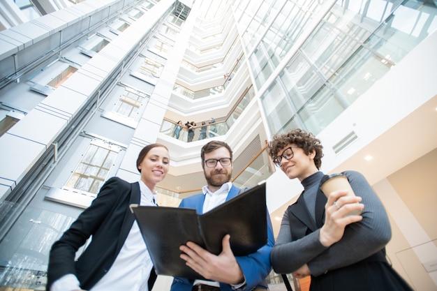 Unten ansicht von zufriedenen geschäftskollegen, die in der bürohalle stehen und gemeinsam zeitungen lesen