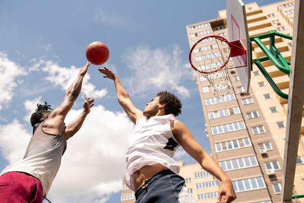 Unten ansicht von zwei interkulturellen rivalen, die versuchen, ball während des trainings am außenplatz in bewegung zu fangen