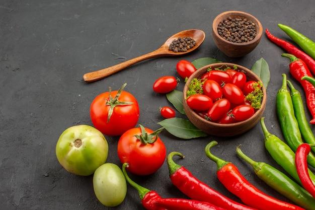 Unten nahe ansicht eine schüssel kirschtomaten scharfe rote und grüne paprika und tomaten schwarzer pfeffer in einem holzlöffel eine schüssel schwarzer pfeffer auf schwarzem hintergrund