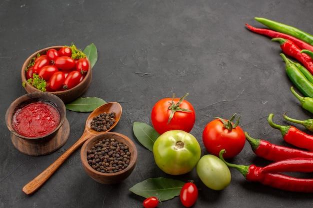 Unten sehen sie eine schüssel mit kirschtomaten, scharfen roten und grünen paprikaschoten und tomaten-lorbeerblättern, schalen mit ketchup und schwarzem pfeffer und einem löffel auf einem schwarzen tisch