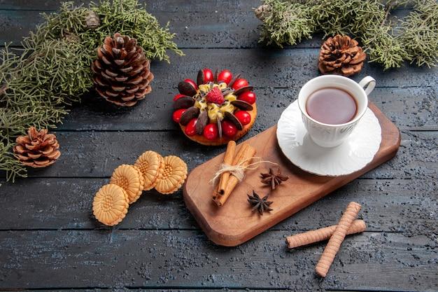 Unten sehen sie eine tasse tee anissamen und zimt auf hölzernem servierteller tannenzapfen beerenkuchen und verschiedene kekse auf dunklem hintergrund