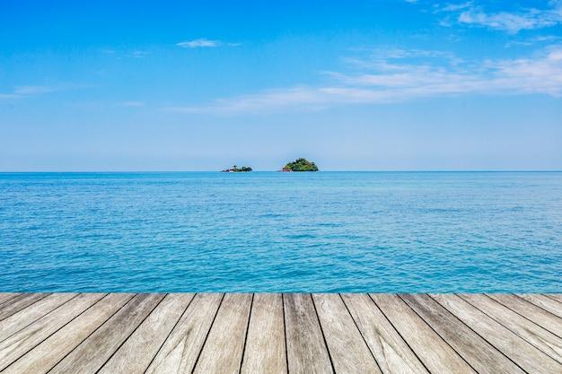 Unter dem blauen himmel, hölzerne plattform neben dem meer.