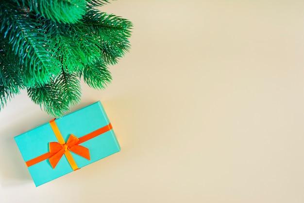 Unter dem neujahrsbaum befindet sich ein geschenk in einer blauen schachtel mit einem roten band, ein bild von oben.