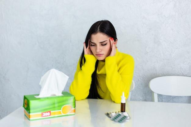 Unter dem wetter. kranke junge frau, die sich schlecht fühlt und sich die nase putzt, während sie eine decke auf den schultern hat und mit geschlossenen augen auf der couch sitzt und einen tisch mit tabletten vor sich hat