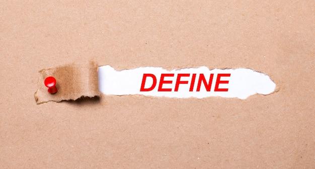 Unter dem zerrissenen kraftpapierstreifen, der mit einem roten knopf befestigt ist, befindet sich ein weißes papier define