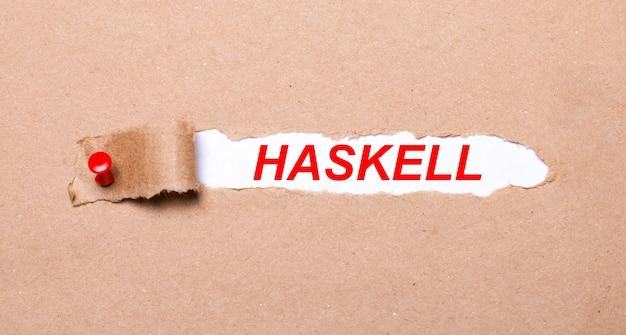 Unter dem zerrissenen kraftpapierstreifen, der mit einem roten knopf befestigt ist, befindet sich ein weißes papier haskell