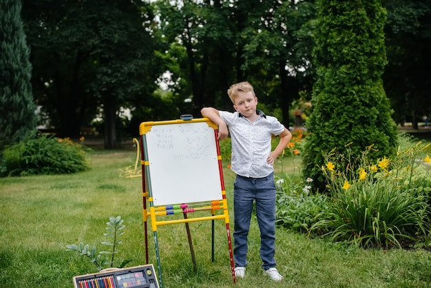 Unter freiem himmel im park schreibt ein schüler beispiele an die tafel. geh zurück zur schule, lerne während der pandemie.