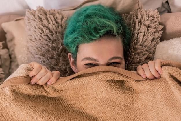 Unter kariert. grünhaarige, fröhliche, lustige frau, die auf einem flauschigen braunen kissen unter einem plaid liegt