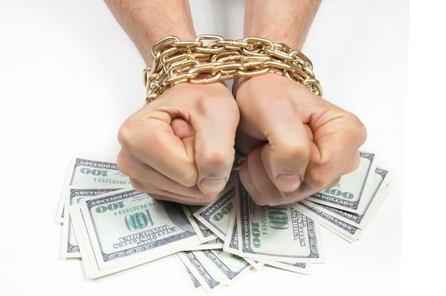 Unter seinen zu fäusten geballten und in eine goldkette gewickelten händen befindet sich ein bündel von hundert dollarnoten