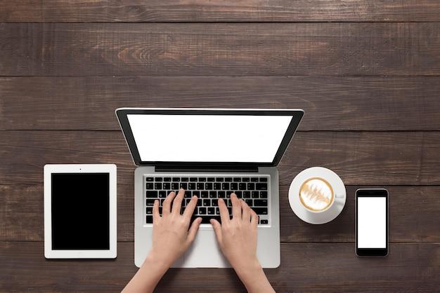 Unter verwendung des laptops, der tablette, des smartphone und des tasse kaffees auf hölzernem hintergrund