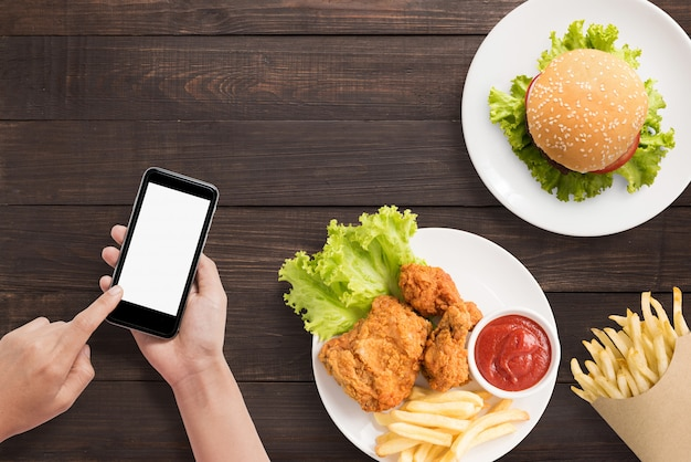 Unter verwendung des smartphone mit burger, pommes-frites und gebratenem huhn stellte auf hölzernen hintergrund ein