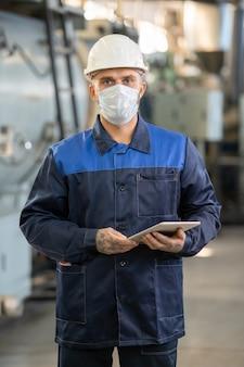 Unteransicht des jungen bärtigen ingenieurs in bauarbeiterhelm mit tablet während der kontrolle der arbeit in der fabrik