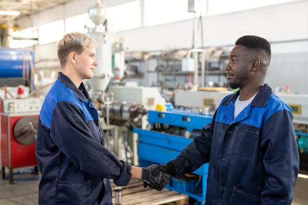 Unteransicht des lächelnden anlagenbesitzers in hemd und krawatte, der mit arbeitern beim treffen mit ihnen in der industrie handshake
