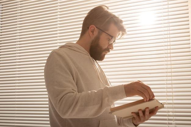 Unteransicht des nachdenklichen stilvollen hipster-mannes, der durch seinen tagesplaner vor den jalousien blättert