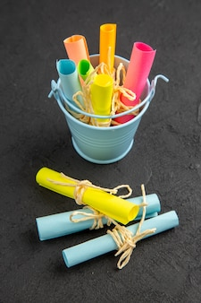 Unteransicht farbige notizpapiere aufgerollte haftnotizen, die mit einem seil in einem kleinen eimer auf einem schwarzen tisch gebunden sind