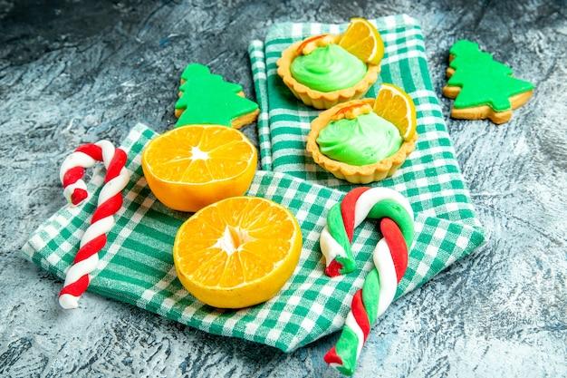 Unteransicht geschnittene orangen weihnachtsbaum bonbons kleine törtchen auf grün-weiß kariertem küchentuch auf grauem tisch