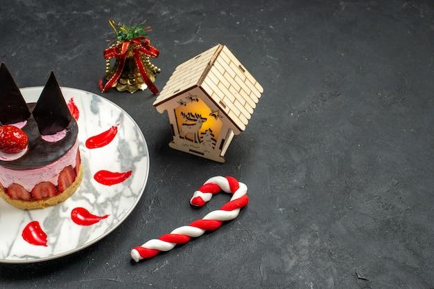 Unteransicht köstlicher käsekuchen mit erdbeeren und schokolade auf ovalem teller weihnachtsspielzeug auf dunklem hintergrund