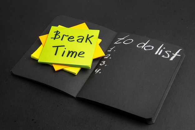 Unteransicht pausenzeit auf haftnotiz to do liste auf schwarzem notizblock auf schwarzem tisch geschrieben