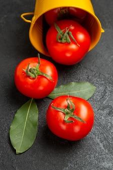 Unteransichtseimer mit roten tomaten auf dunklem hintergrund Kostenlose Fotos