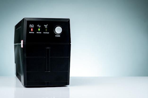 Unterbrechungsfreie stromversorgung. notstrom-usv mit der batterie lokalisiert auf tabelle. ups für pc. ausrüstung für computersystem im büro für sicherheit. stromschutzlösungen von zu hause bis zum rechenzentrum.