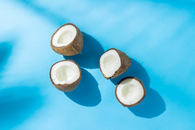 Unterbrochene kokosnuss auf einer blauen oberfläche unter natürlichem licht mit schatten. hartes licht. konzept der ernährung, gesunde ernährung, erholung in den tropen, urlaub und reisen, vitamine. flachgelegt, draufsicht.