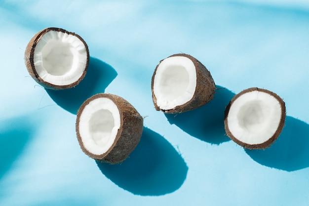 Unterbrochene kokosnuss auf einer blauen oberfläche unter natürlichem licht mit schatten. hartes licht. konzept der ernährung, gesunde ernährung, erholung in den tropen, urlaub und reisen, vitamine.