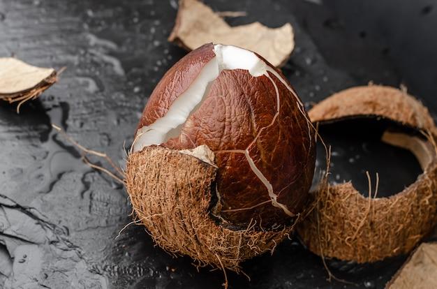 Unterbrochene reife kokosnuss auf schwarzem schieferstein