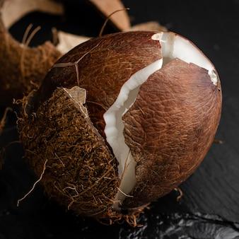 Unterbrochene rohe kokosnuss auf schwarzem schiefersteinhintergrund.
