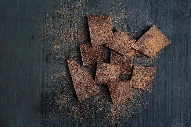 Unterbrochene schokoladenstücke und kakaopulver auf schwarzem hintergrund. kopieren sie platz.