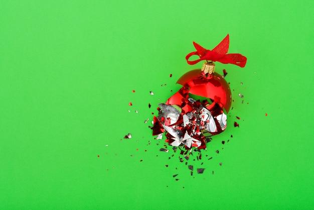Unterbrochene weihnachtskugel auf grünem hintergrund