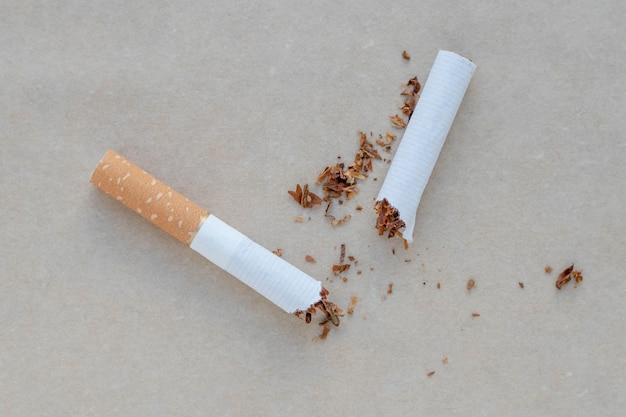 Unterbrochene zigarette auf einem neutralen hintergrund.