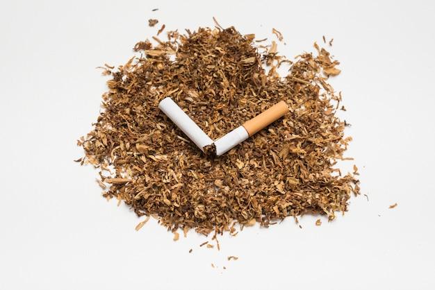 Unterbrochene zigarette auf tabak gegen weißen hintergrund