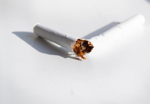 Unterbrochene zigarette auf weißem hintergrund, raucherentwöhnung