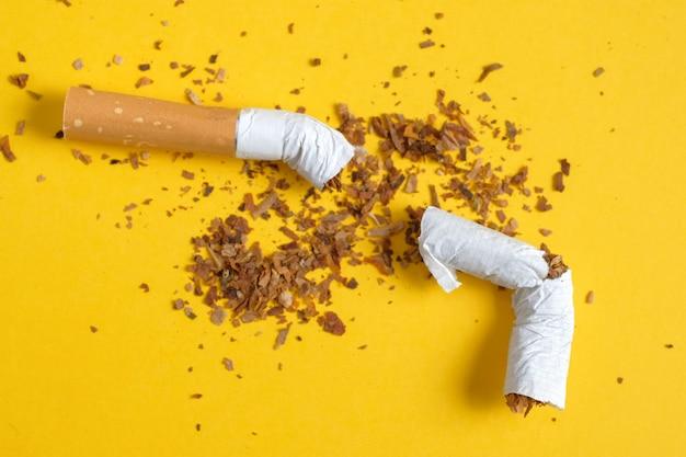Unterbrochene zigarette zur hälfte mit einer reihe des zerstreuten tabaks auf gelb