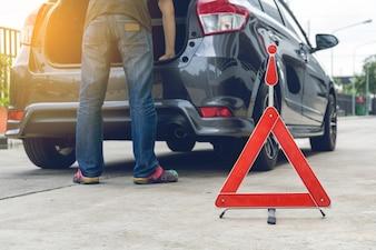 Unterbrochenes Autozeichen auf einer Straße mit einem aufgegliederten Auto