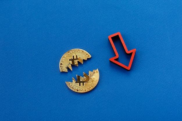 Unterbrochenes bitcoin, kryptowährung, die mit rotem pfeil fällt