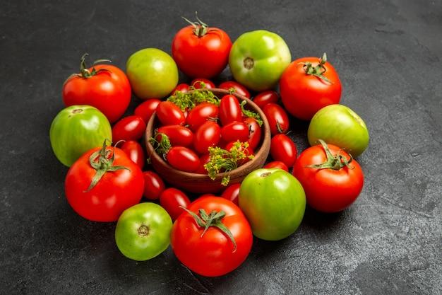 Untere ansicht kirschrot und grüne tomaten um eine schüssel mit kirschtomaten auf dunklem hintergrund