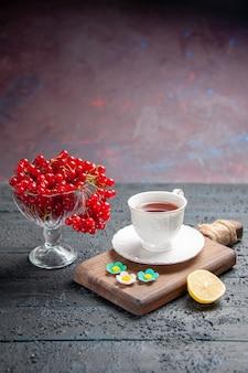 Untere ansicht rote johannisbeere in einem glas eine tasse tee auf einer schneidebrettscheibe zitrone auf dunklem hintergrund