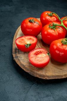 Untere hälfte ansicht frische rote tomaten holzbrett auf dunklem tisch