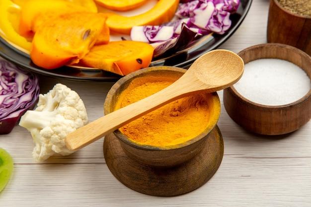 Untere hälfte ansicht geschnittenes gemüse und obst kürbis paprika kaki rotkohl auf schwarzem teller gewürz in kleinen schalen holzlöffel auf holztisch