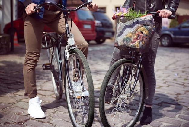 Unterer abschnitt eines paares, das mit fahrrädern auf der straße steht