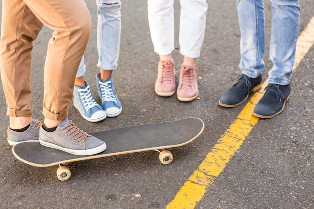 Unterer teil der hip freunde und skateboard auf der straße