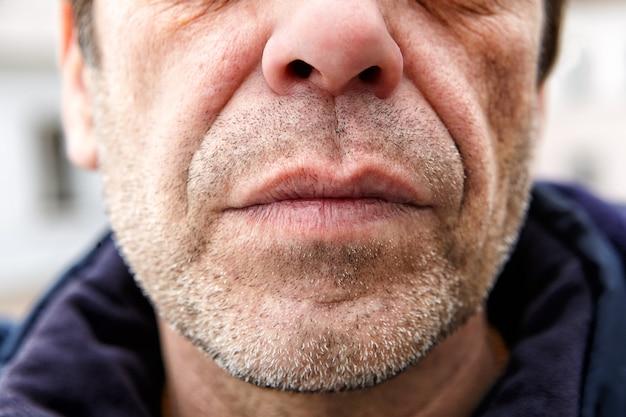 Unterer teil des unrasierten gesichts eines mannes mittleren alters, 50 jahre alt, ist es möglich, dass er arbeiter ist.
