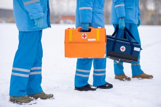 Unterer teil von drei sanitätern in blauer arbeitskleidung und handschuhen, die erste-hilfe-sets halten, während sie auf schnee stehen