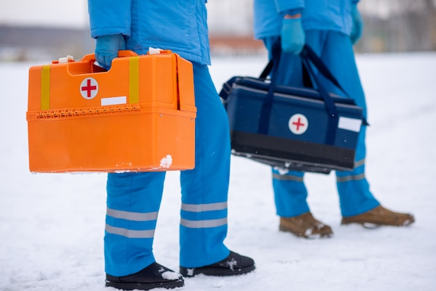 Unterer teil von zwei sanitätern in uniform und handschuhen, die erste-hilfe-sets tragen, um kranken menschen zu helfen und sie zu retten