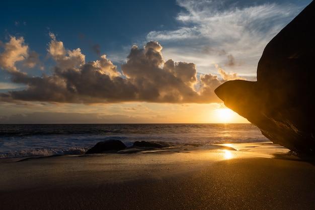 Untergehende sonne über riesigen felsen am strand