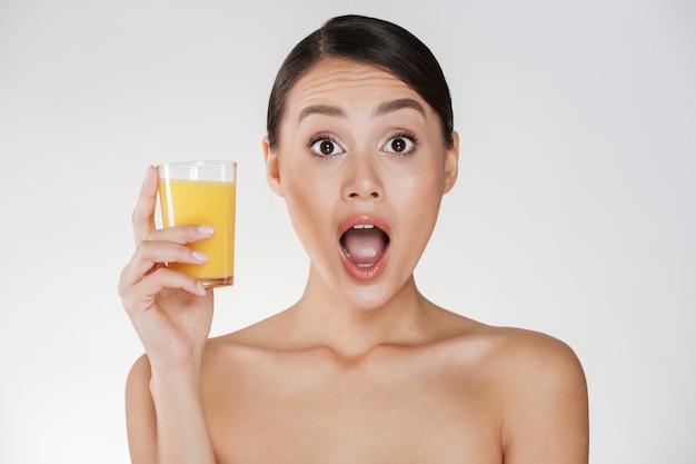 Unterhaltendes foto der lustigen frau mit dem dunklen haar im brötchen, das transparentes glas frisch-zusammengedrückten orangensaft, lokalisiert über weißer wand hält