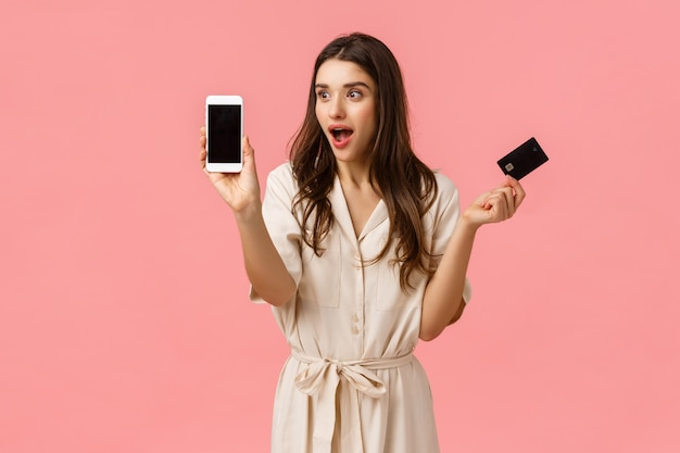 Unterhaltene und überraschte, schöne kaukasische frau im kleid, kreditkarte halten und etwas zeigen, das am telefonschirm erstaunlich und kühl ist und die rosa wand froh stehen