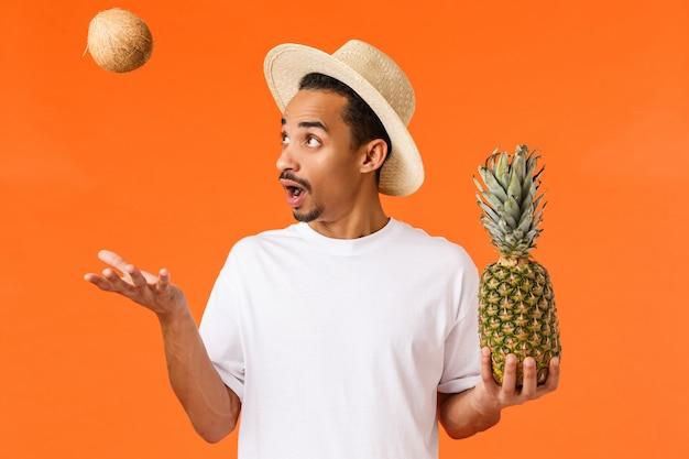 Unterhaltener glücklicher männlicher reisender, tourist, der das fünf-sterne-hotel im tropischen land genießt, die früchte besichtigt, fängt kokosnuss und hält die ananas und entspannt sich unter der sonne und steht orange