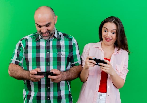 Unterhaltenes erwachsenes paar, das spiel auf handys spielt